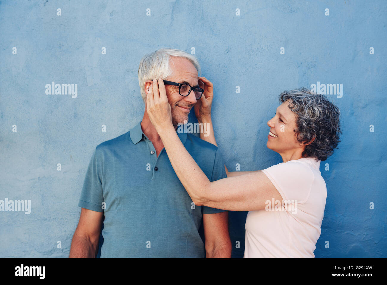 Portrait of woman adjusting the eyeglasses on her husband against blue background. Mature couple together on a blue - Stock Image