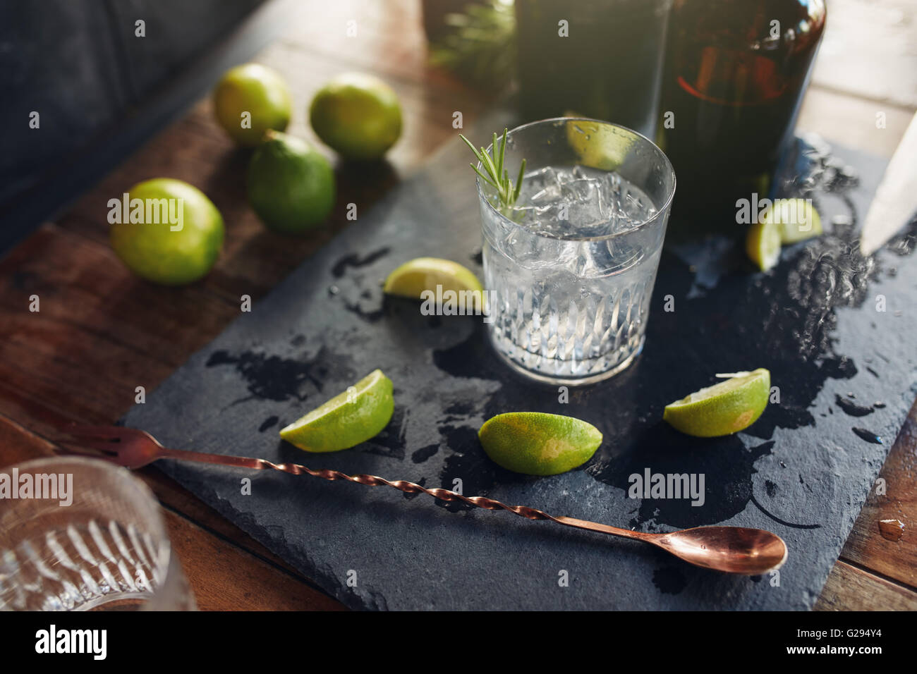 Close up of fresh made cocktail drink with lemon slices and spoon on the board. - Stock Image