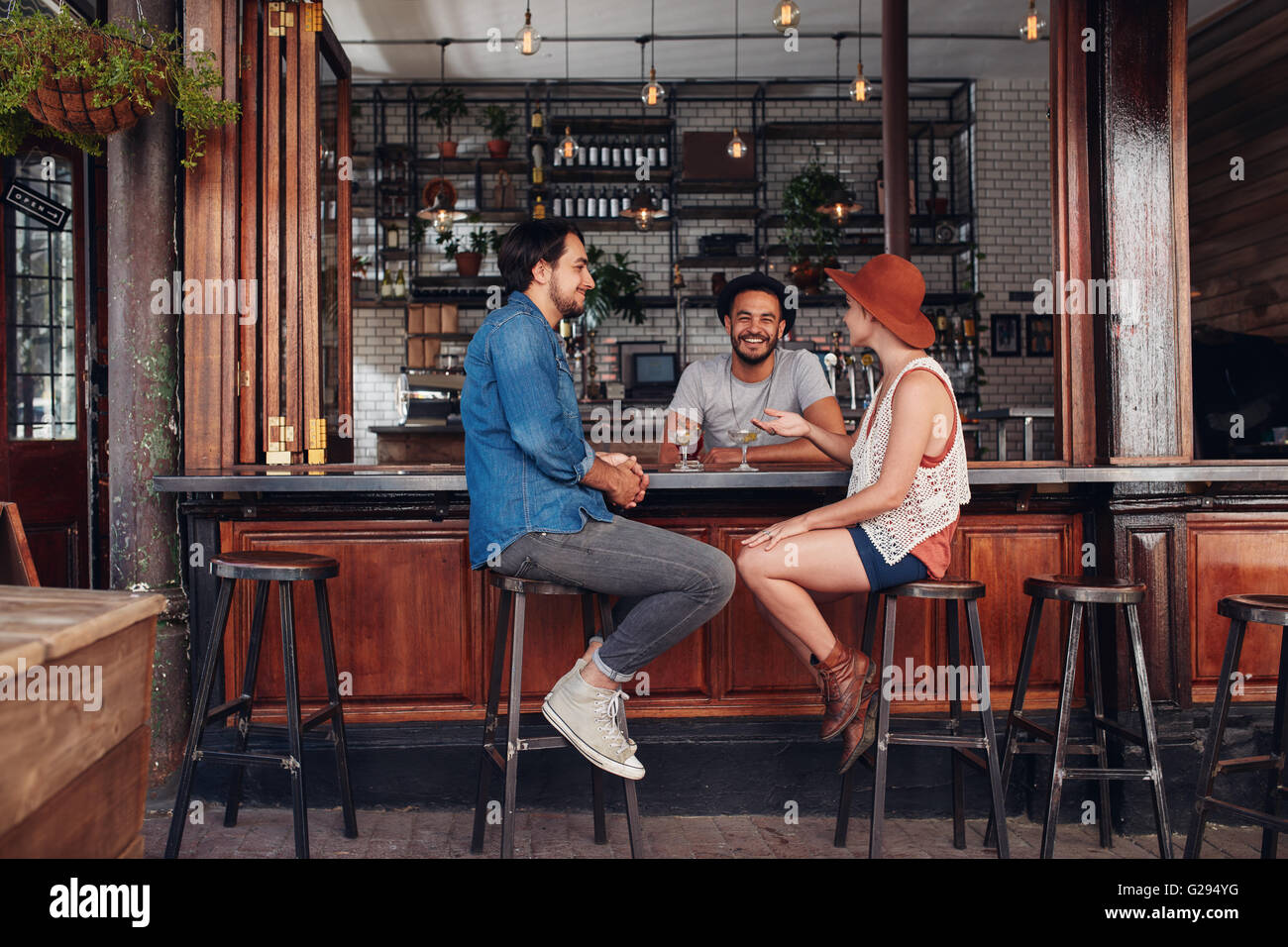 Group of young people sitting in a cafe and talking. Young men and women meeting at cafe table. - Stock Image