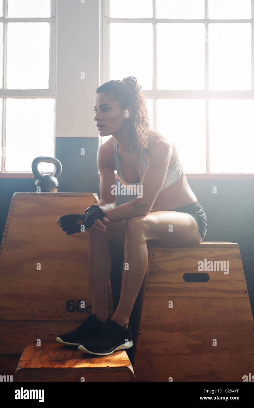 Muscular young woman sitting on a box at gym after her fitness training. Female athlete taking break after workout - Stock Image
