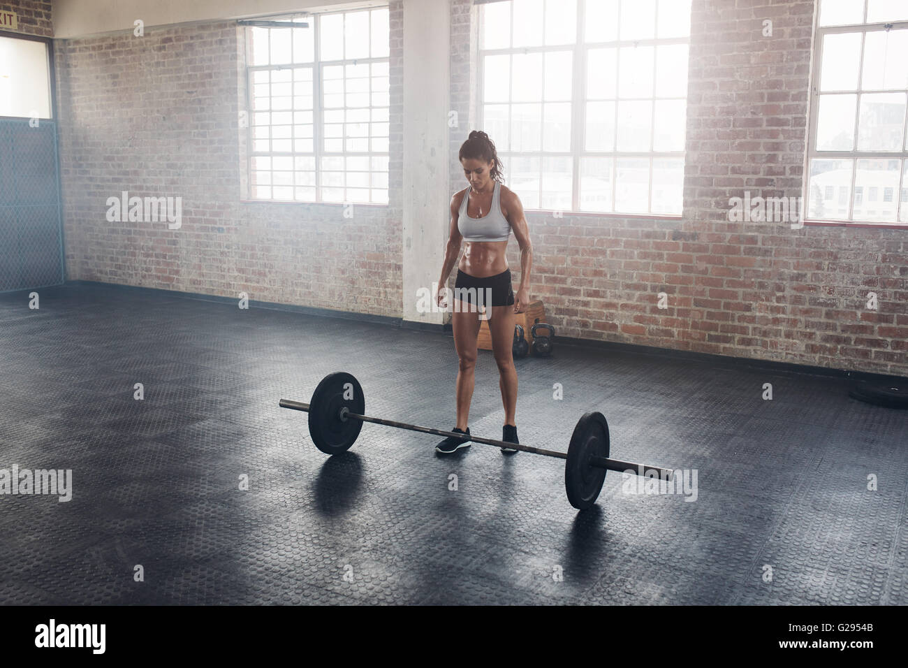 Full length portrait of muscular young woman standing at gym with barbells on floor. Strong crossfit female at gym. - Stock Image