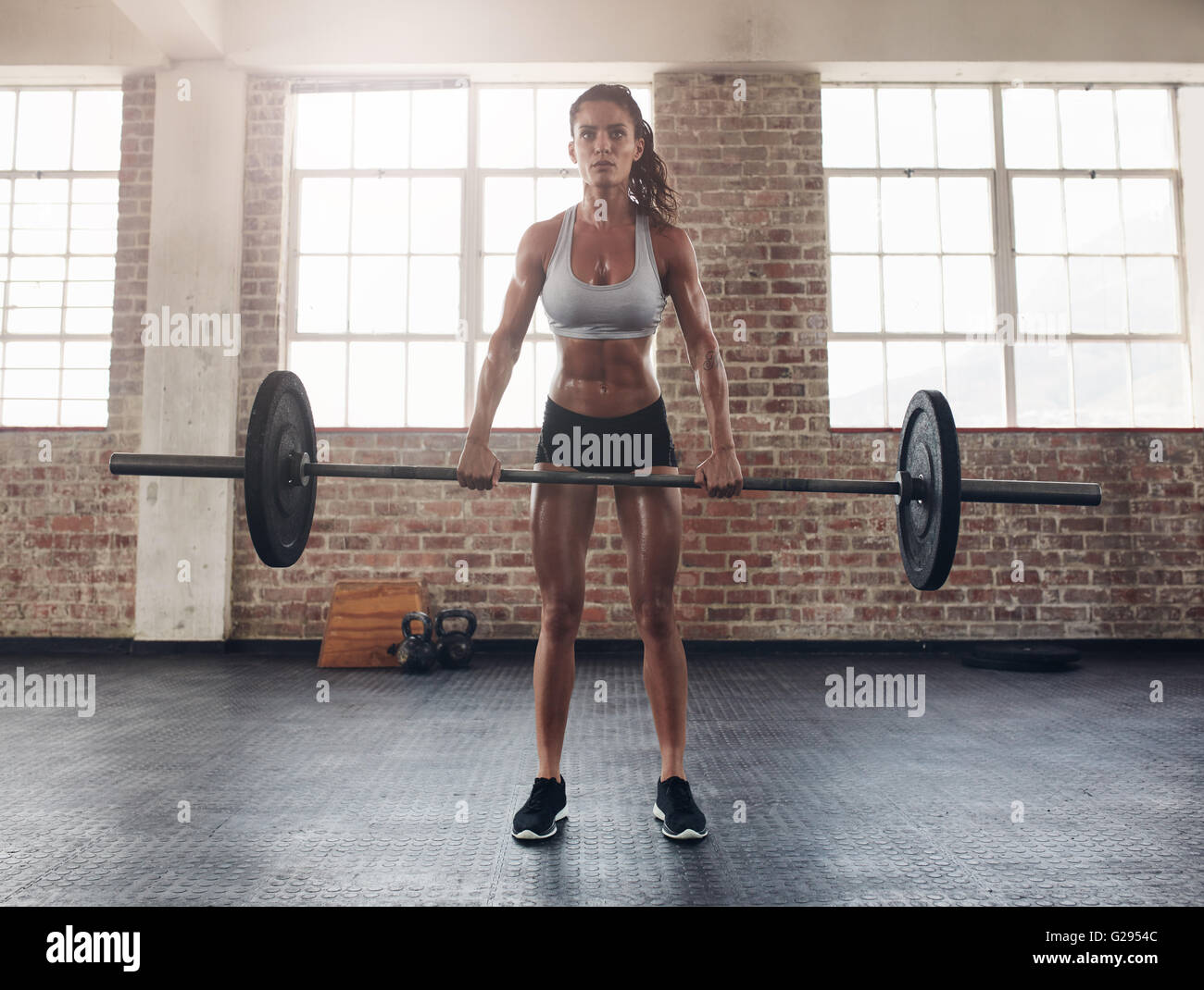 Full length image of tough young woman exercising with barbell. Determined female athlete lifting heavy weights. - Stock Image