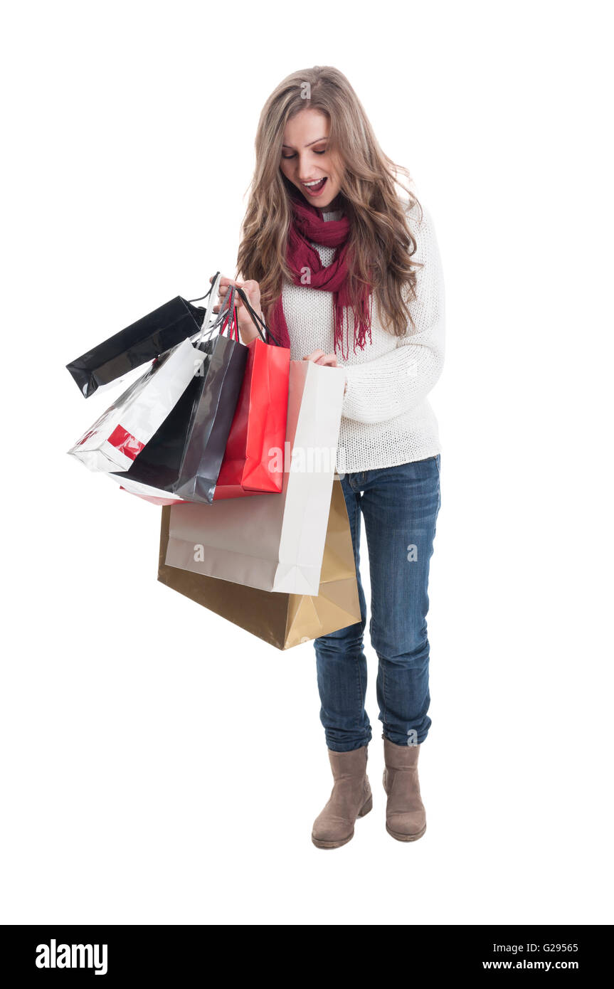Enthusiastic shoping girl looking at what she bought - Stock Image
