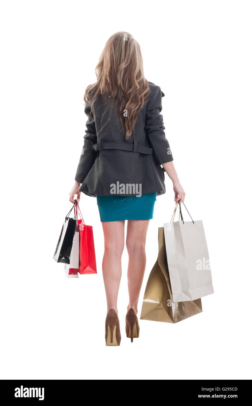 Beautiful shopping girl walking. Photo taken from behind on white background Stock Photo