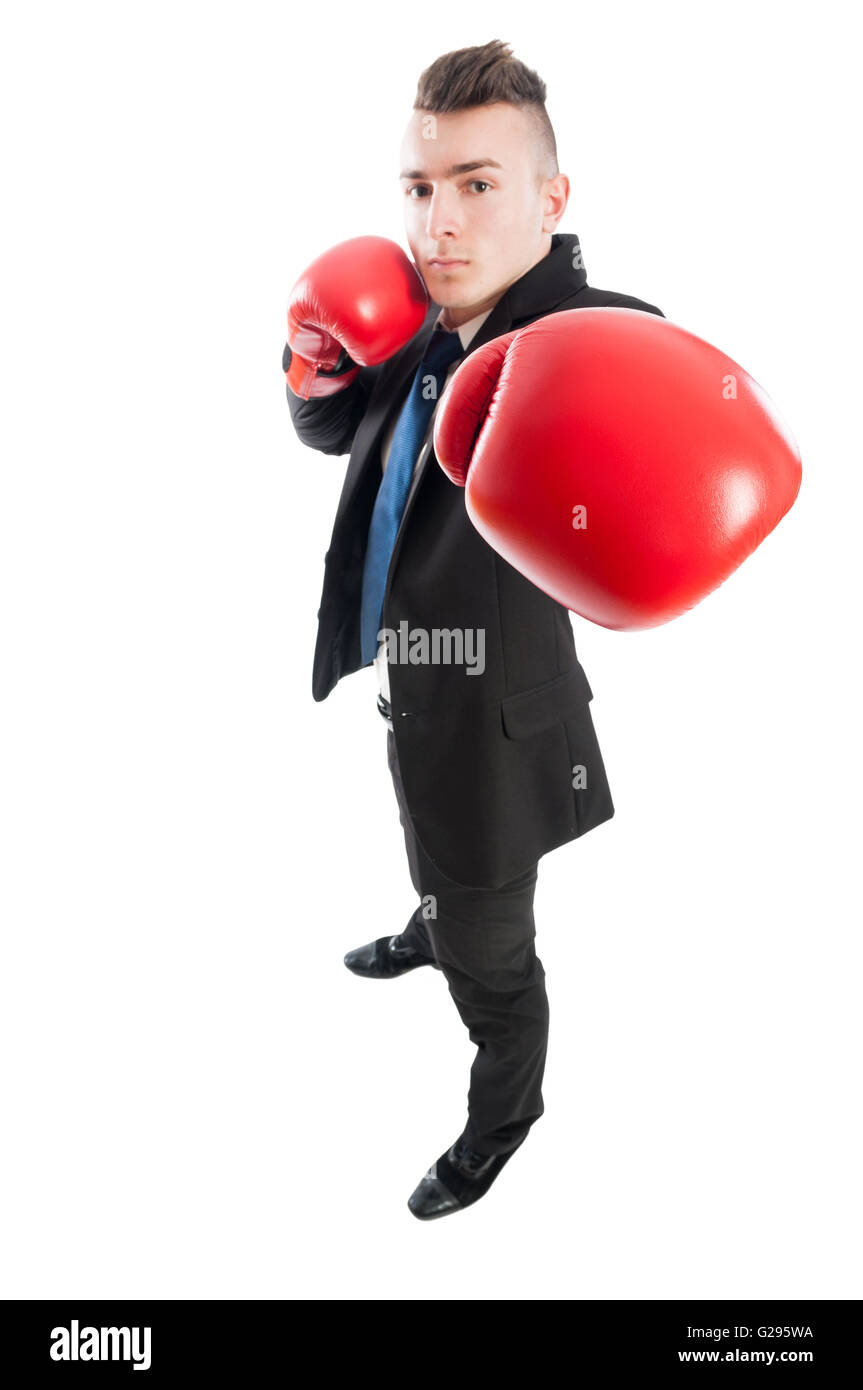 Confident and competitive business man punching the camera with red boxing gloves - Stock Image