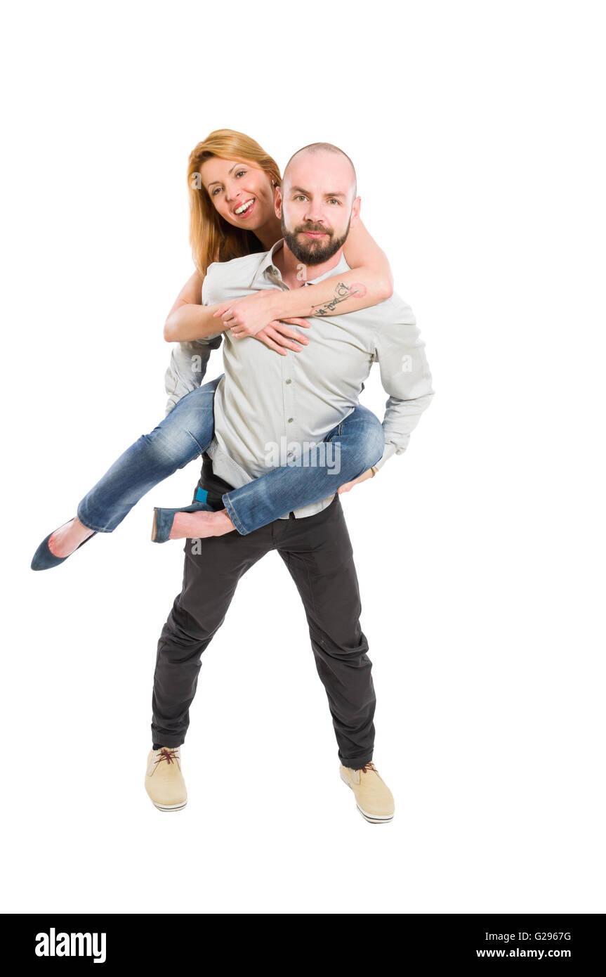 Smiling wife on husband's back isolated on white studio background - Stock Image