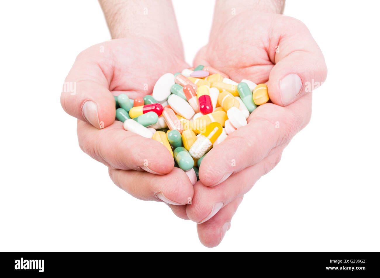Both hands holding bunch of pills. Overdose or abuse concept on white background - Stock Image