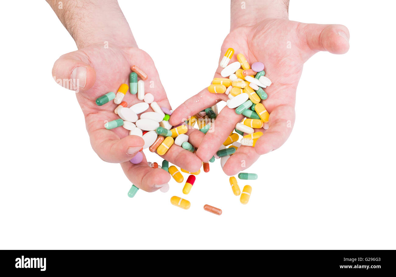 Pills abuse or painkillers concept with dramatic tense or strained hands holding pills - Stock Image