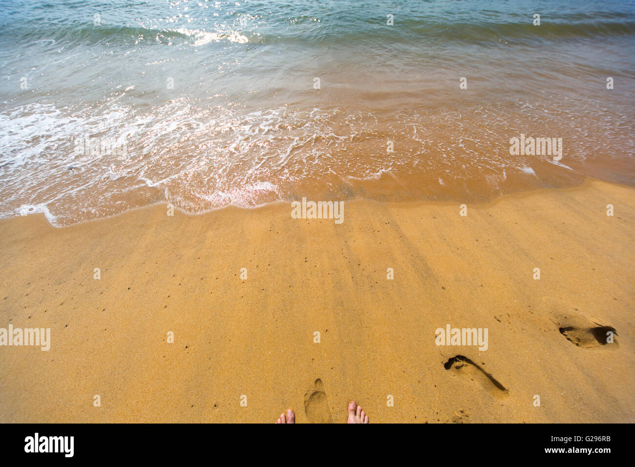Footprints and human feet on the beach - Stock Image