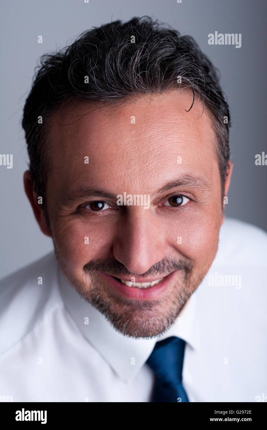 Portrait of a friendly, reliable and successful business man wearing white shirt and blue tie or necktie - Stock Image