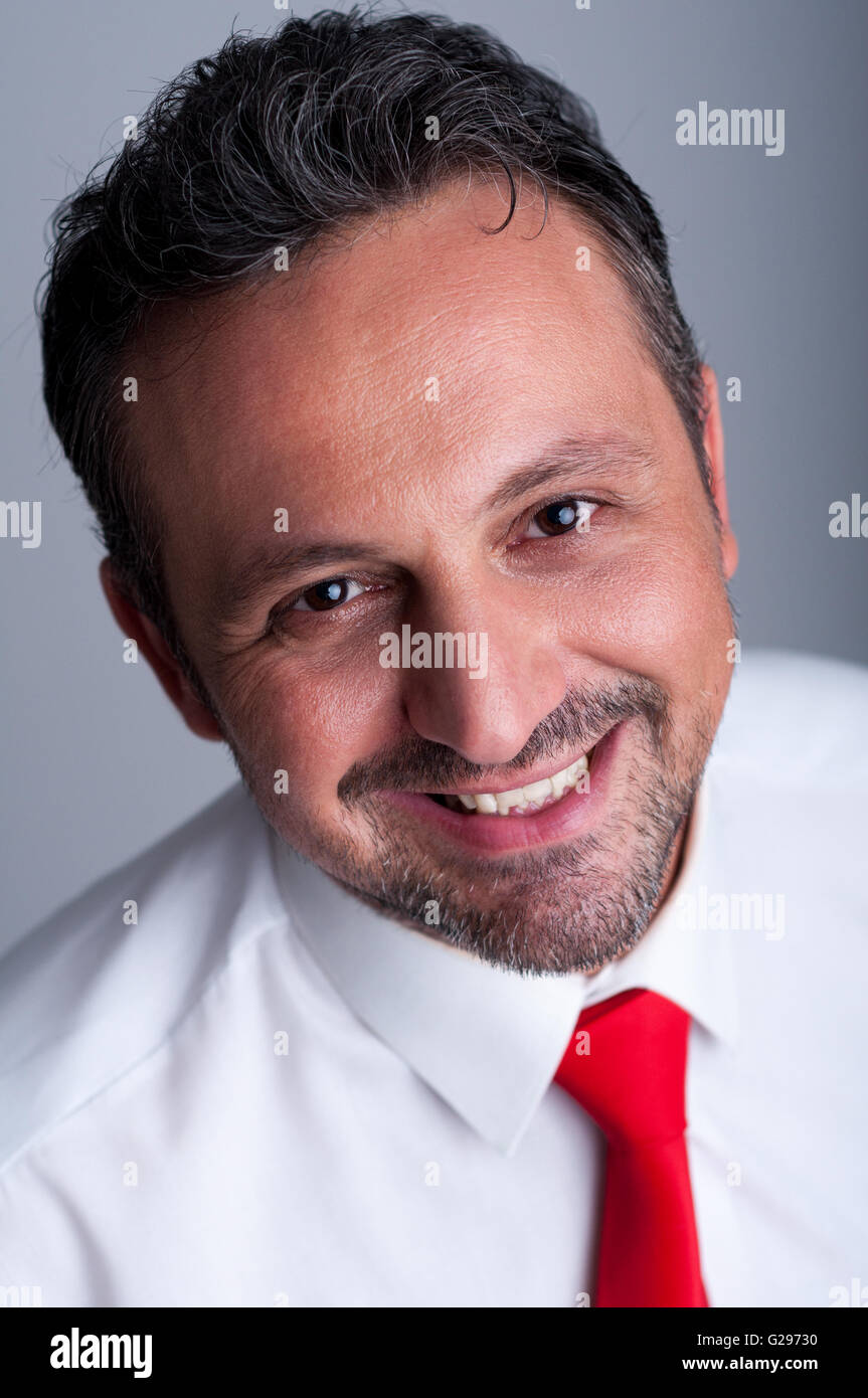 Friendly and reliable smiling politician face portrait with red tie or necktie - Stock Image
