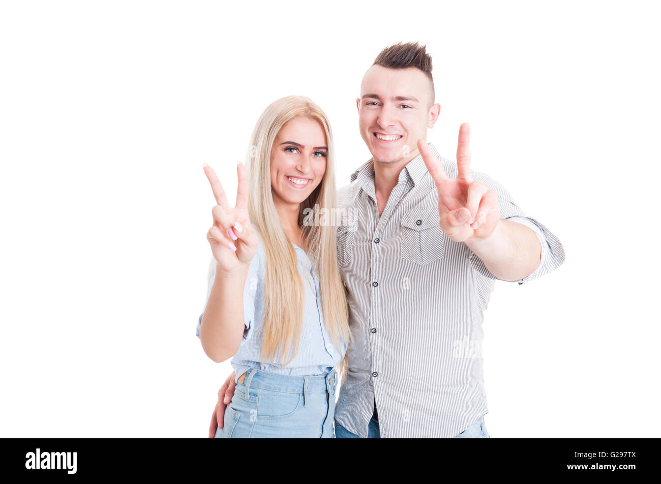 Lovely young couple showing peace or victory sign on white studio background Stock Photo