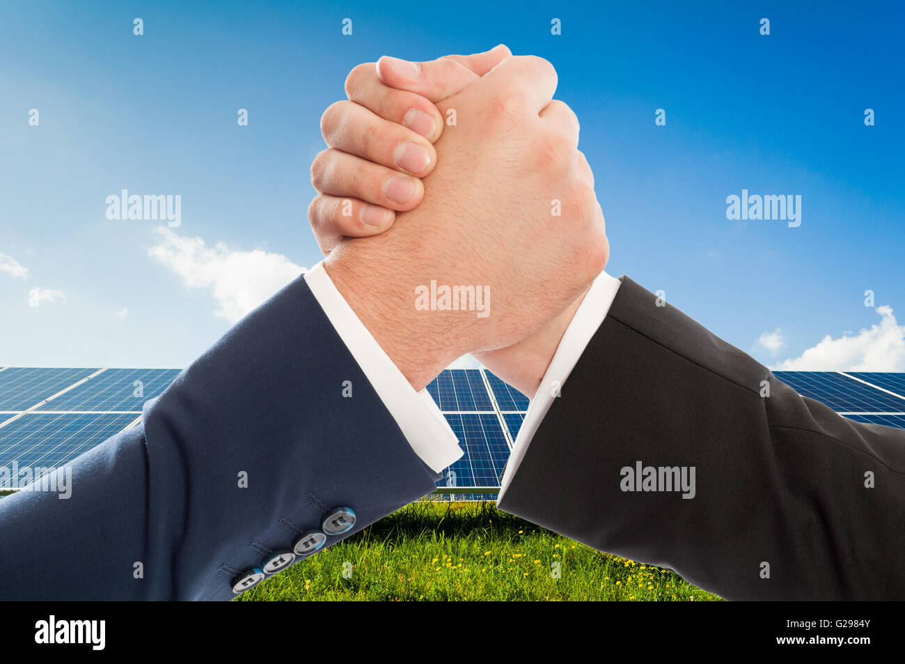 Businessmen handshake as teamwork on solarpower photovoltaic panel background. Renewable energy partnership agreement - Stock Image