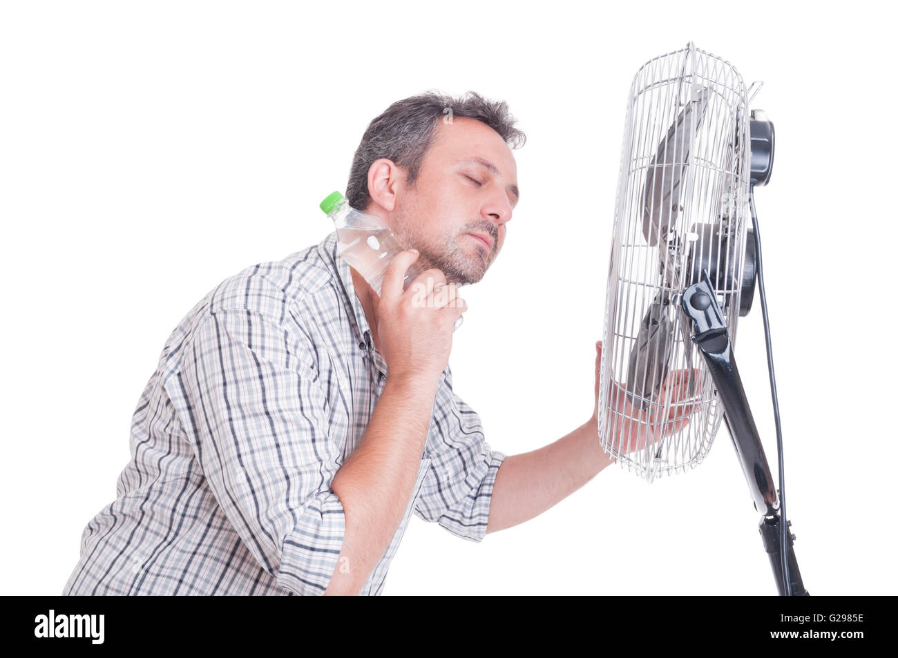 Man cooling down in front of blowing fan holding a bottle of cold water on the neck Stock Photo
