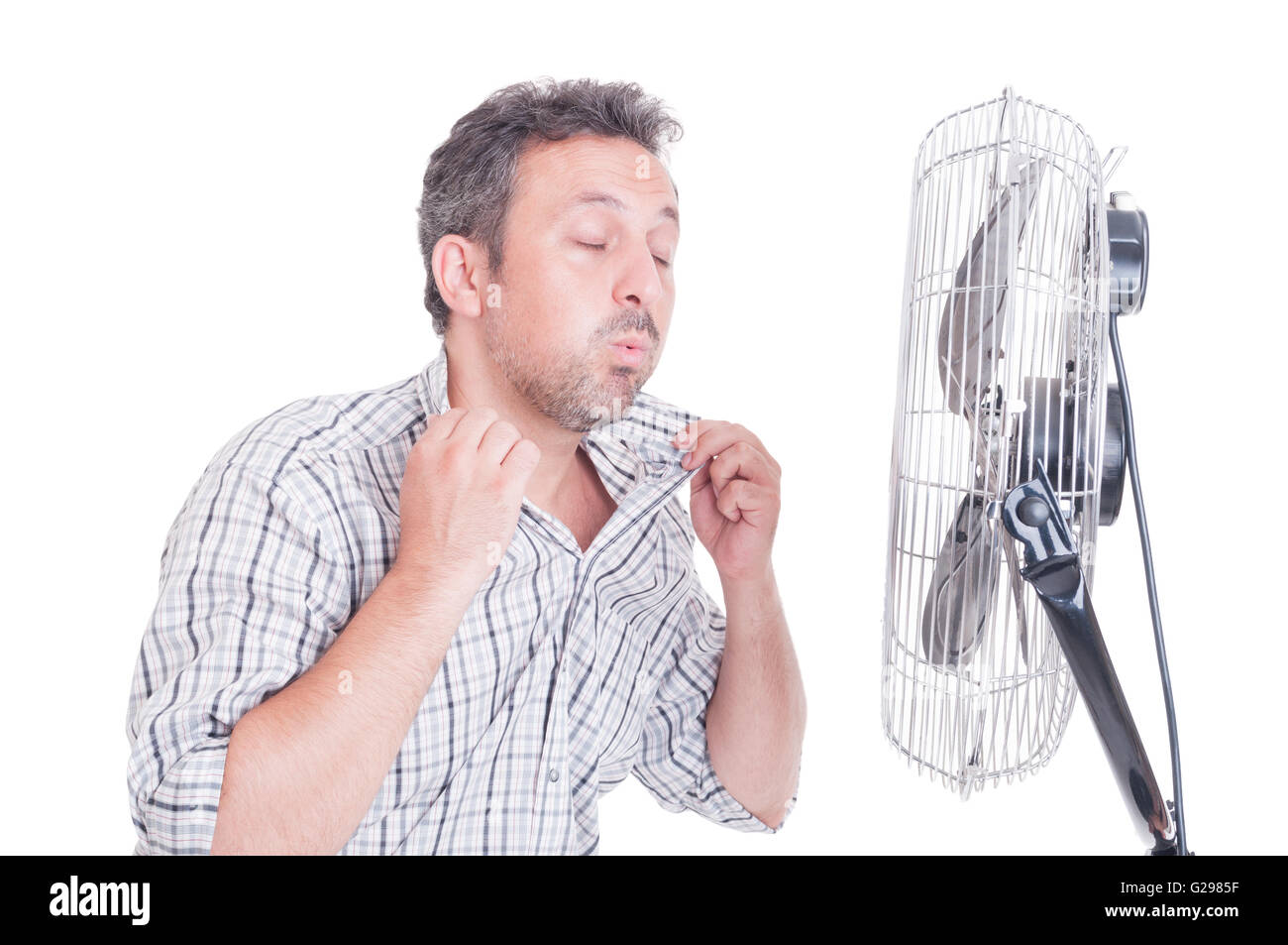 Sweaty man opening shirt in front of cooling fan as refreshing in hot summer concept - Stock Image