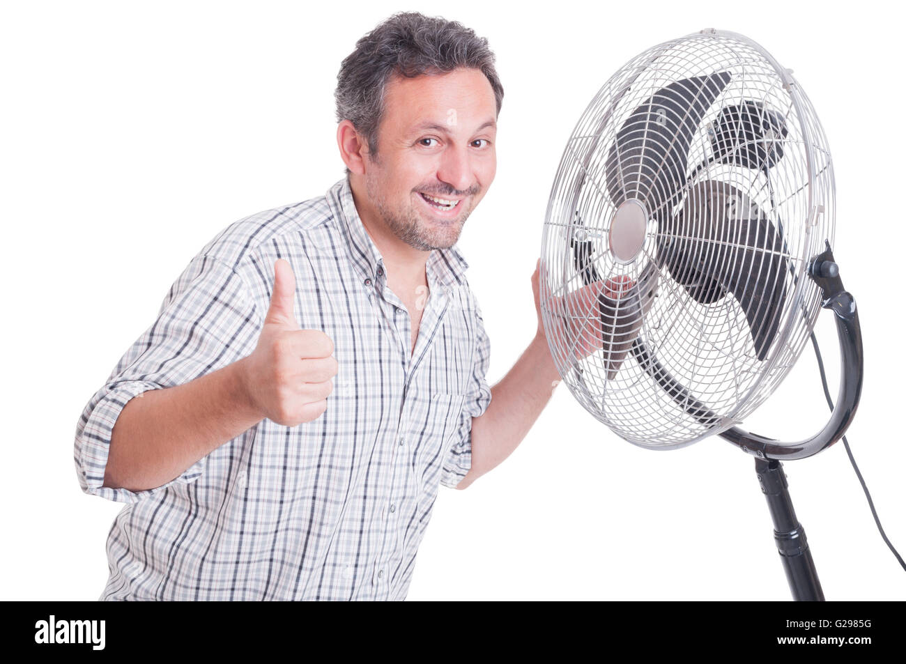 Smiling man showing like gesture in front of blowing cooler as summer heat concept - Stock Image