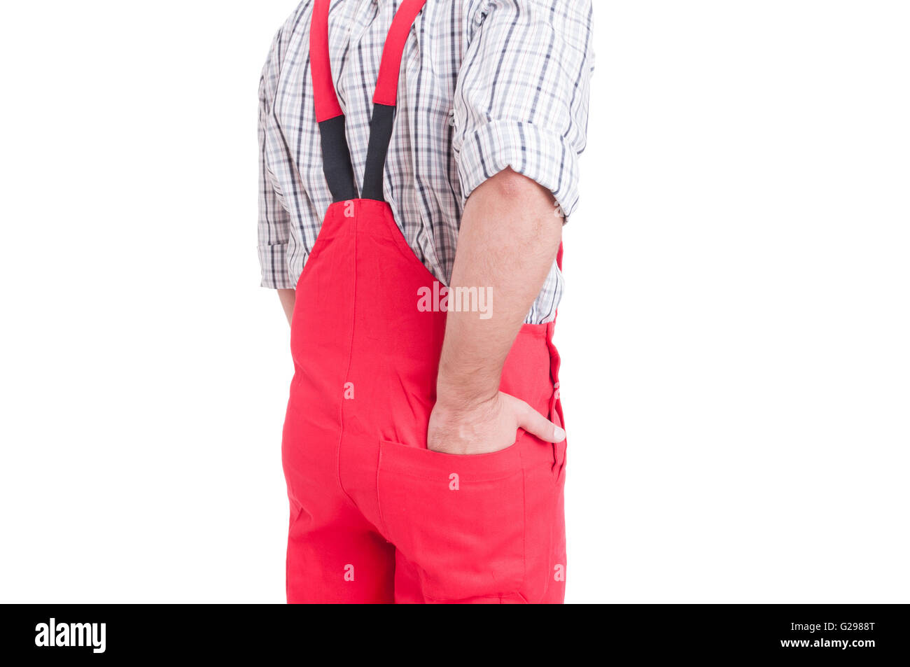 man holding hand inside back pocket of rompers or coveralls isolatd on white - Stock Image