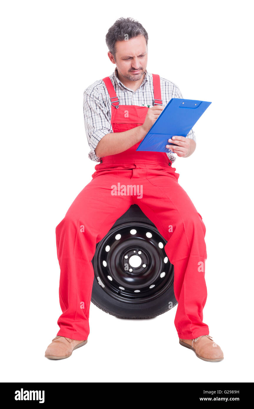 Concentrated mechanic writting on a clipboard while sitting on a wheel tire - Stock Image