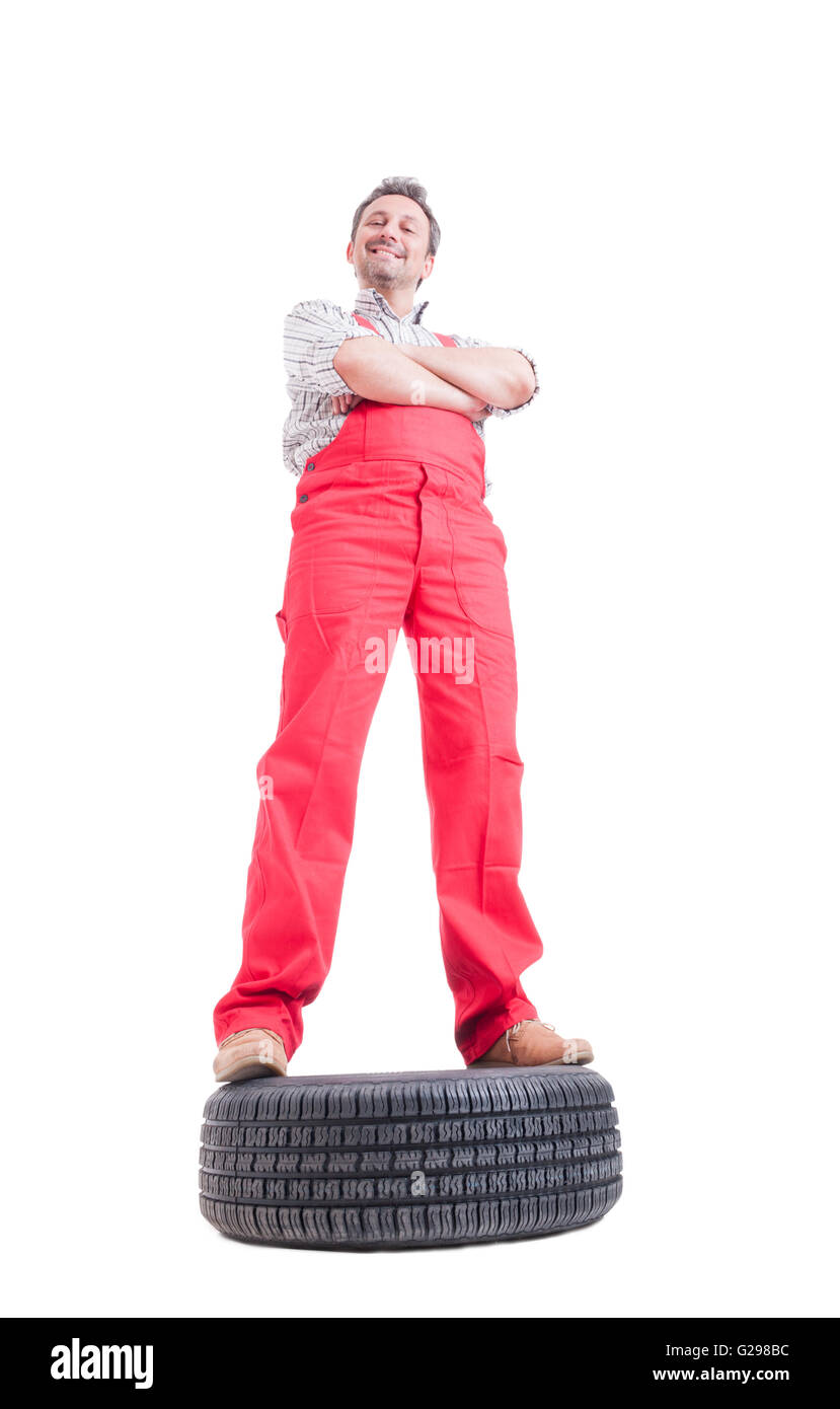 Hero shot of confident mechanic standing on a car wheel isolated on white - Stock Image