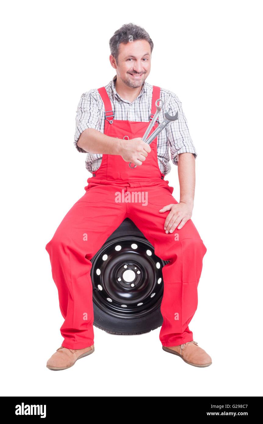 Trustworthy car mechanic holding keys or wrenches - Stock Image