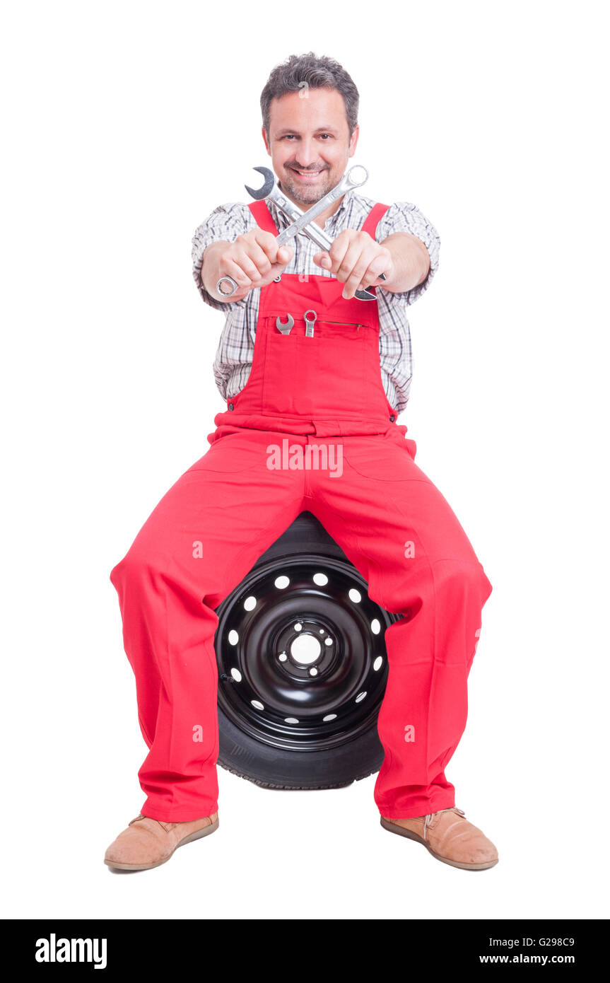 Car mechanic holding crossed spanners or wrenches sitting on wheel - Stock Image