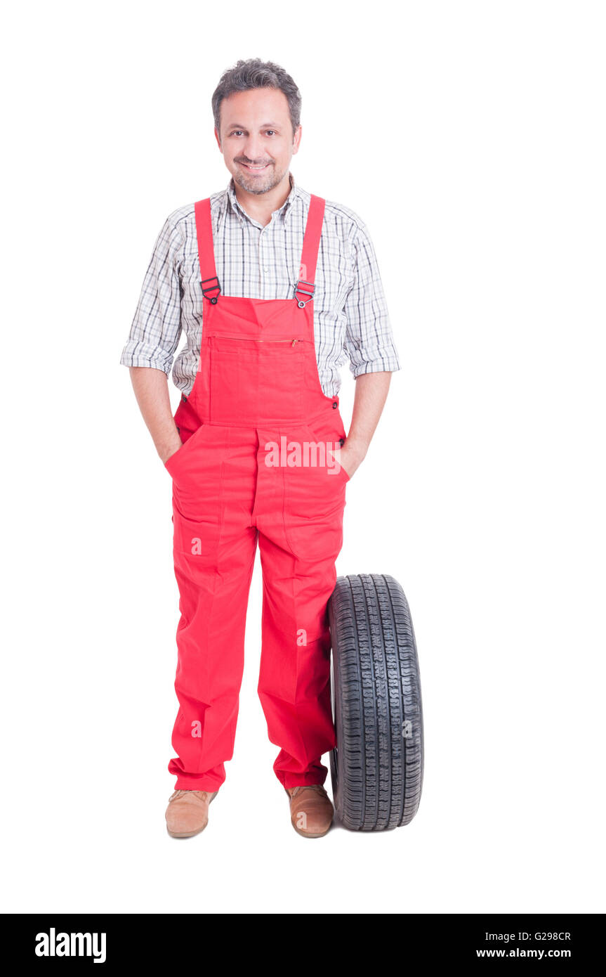 Friendly and trustworthy mechanic standing with hands in pockets newa a wheel tire isolated on white - Stock Image