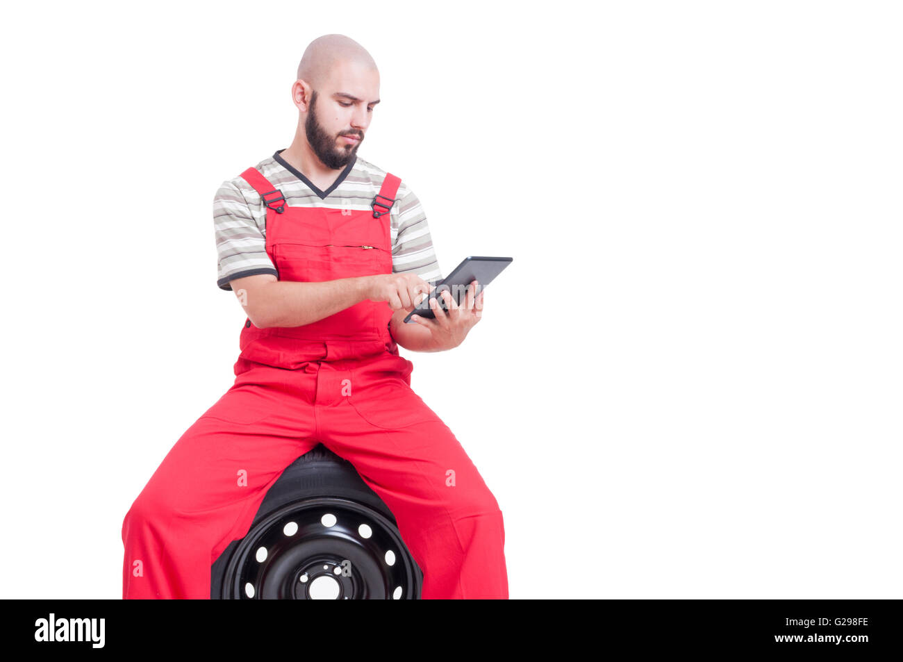 Mechanic using wireless tablet sitting on car wheel. He wears red rompers isolated on white - Stock Image