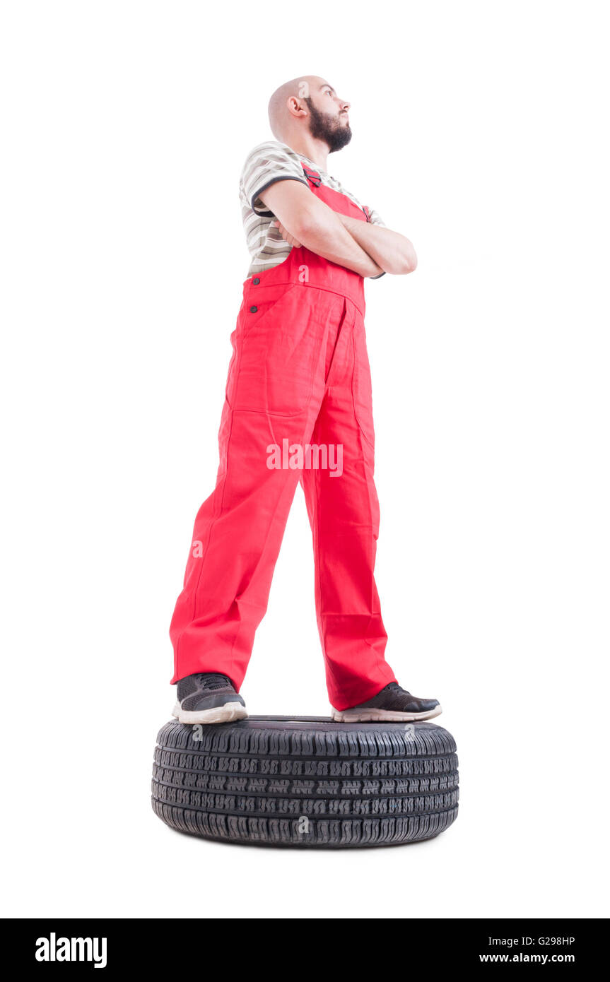 Hero shot in low angle of mechanic standing on car wheel looking up isolated on white - Stock Image