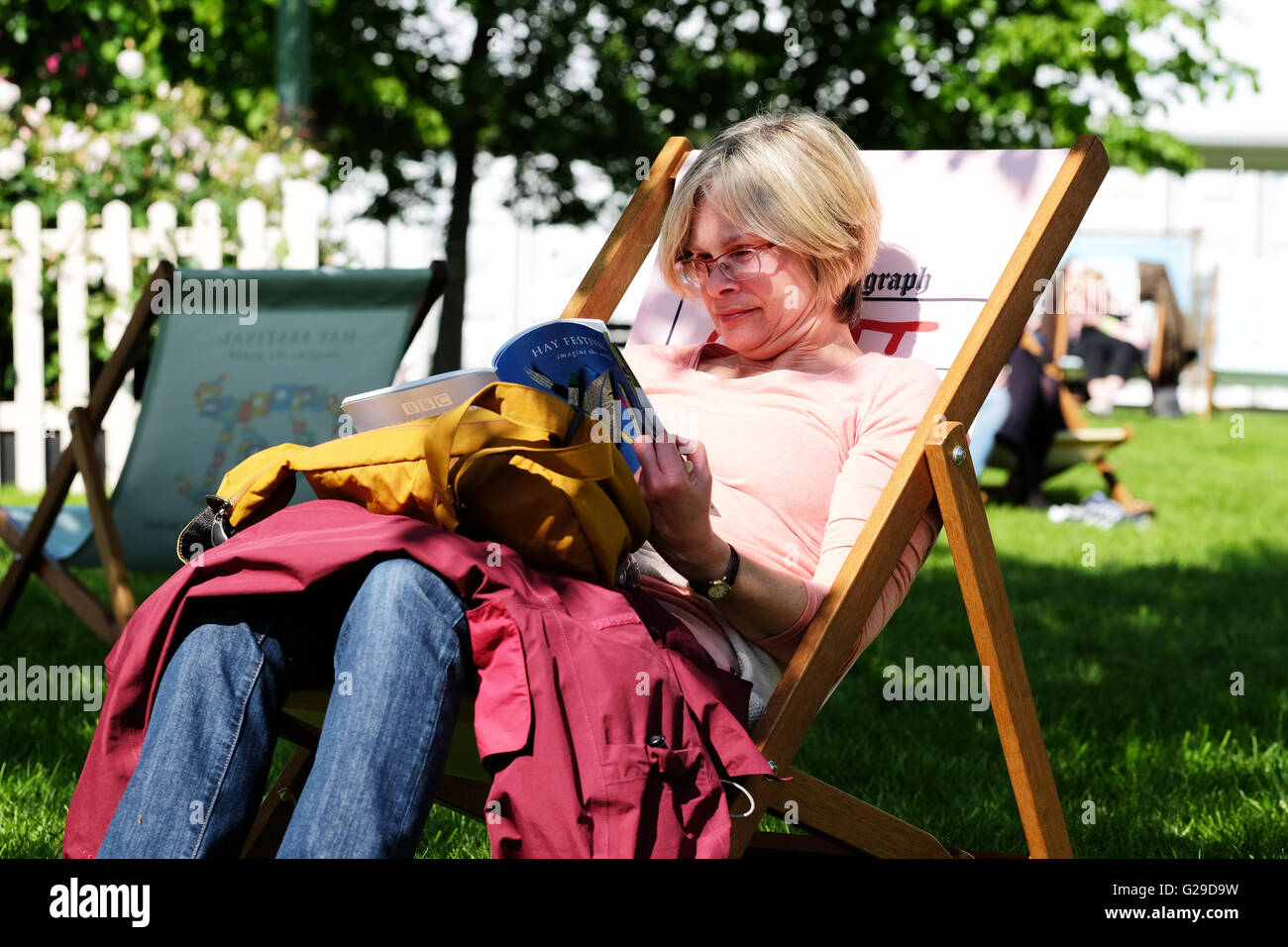 Hay Festival, Hay on Wye, Wales, UK May  2016. Opening day for this years literary and arts festival a woman sits - Stock Image