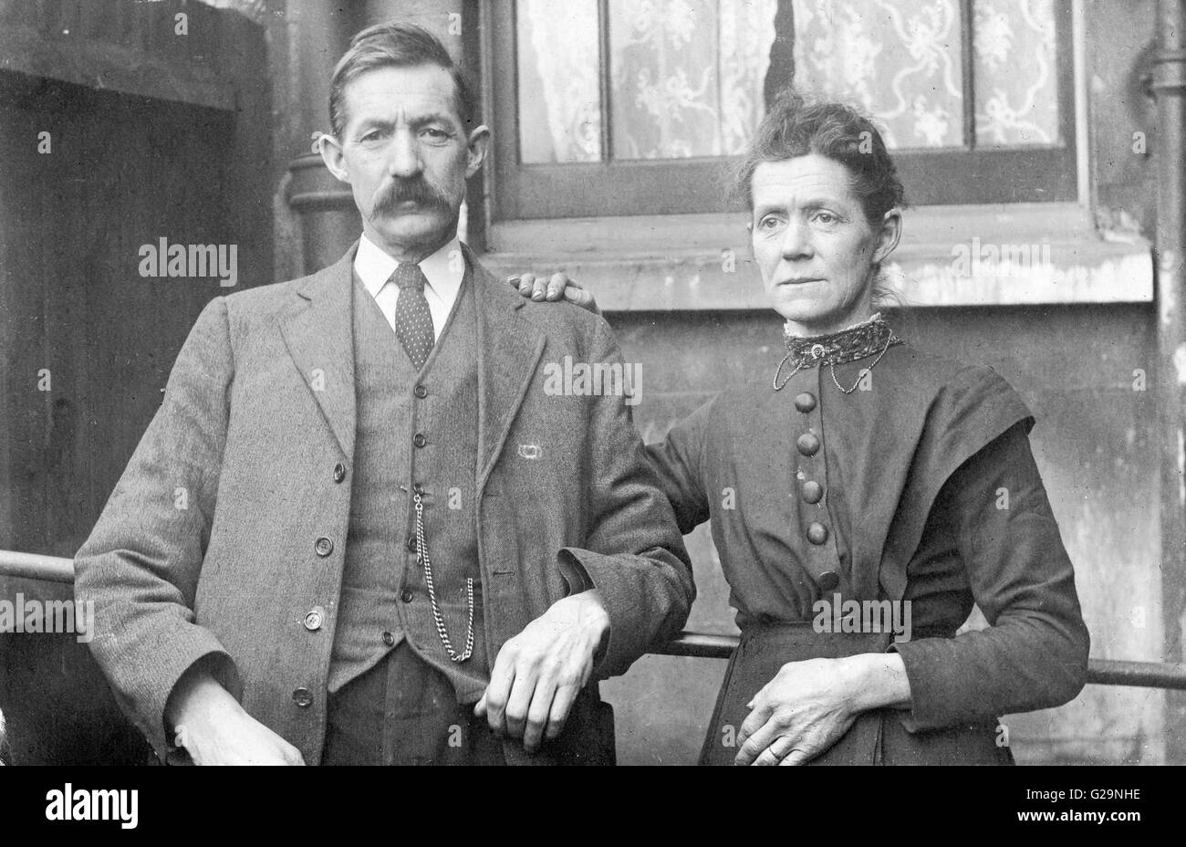 England, 1927. Black and white portrait of middle aged couple posing, facing viewer. Man with moustache, suit, waistcoat - Stock Image