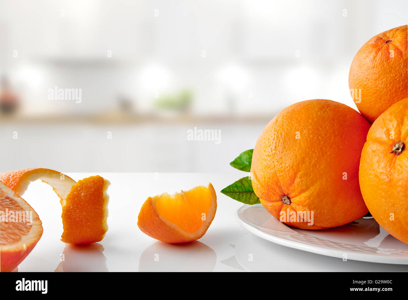 Group of oranges on a plate and sections on white glass table in the kitchen. Horizontal composition. Front view Stock Photo