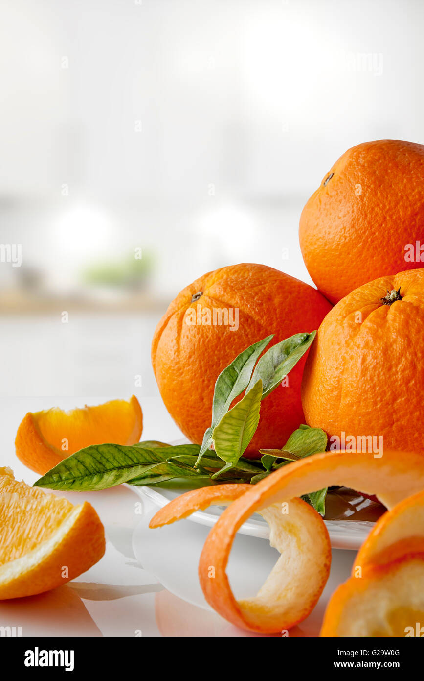 Group of oranges on a plate and sections on white glass table in the kitchen. Vertical composition. Front view Stock Photo