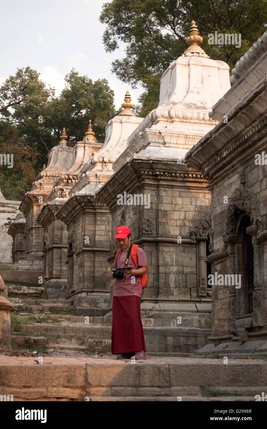 Monk with camera at Pashupatinath Temple, Kathmandu, Nepal - Stock Image
