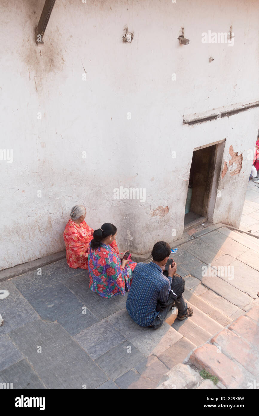 People sitting at the Pashupatinath Temple looking at mobile phones, Kathmandu, Nepal - Stock Image