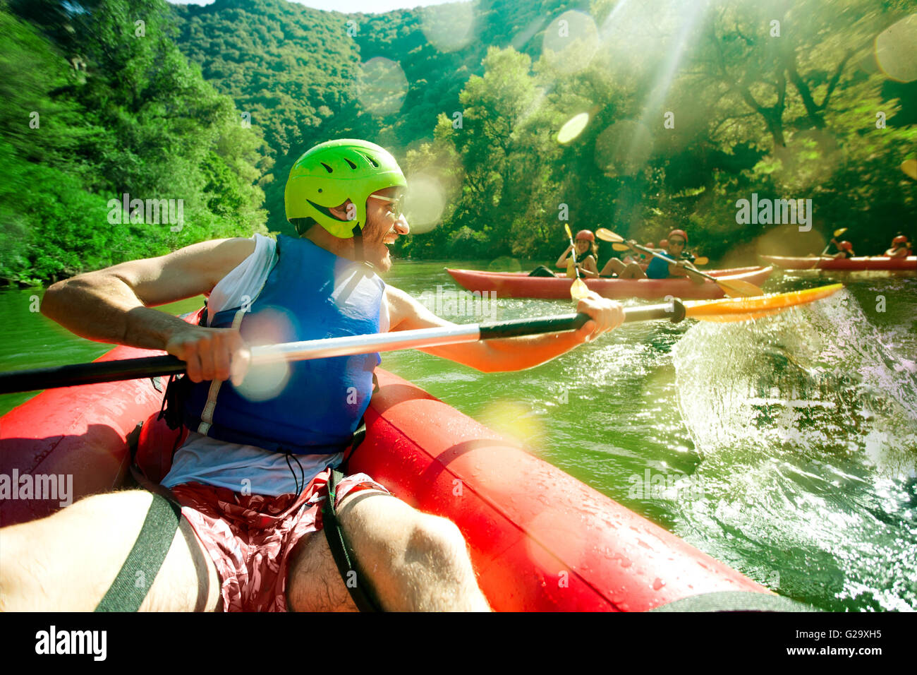 A young main in red inflatable canoe having fun splashing over his friends in a river. - Stock Image