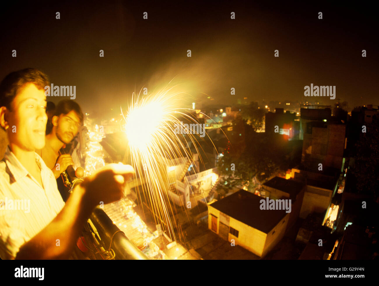 Two male teenagers light a sparkler on the rooftop of the Vivek guesthouse in celebration of Diwali.The Diwali festival - Stock Image