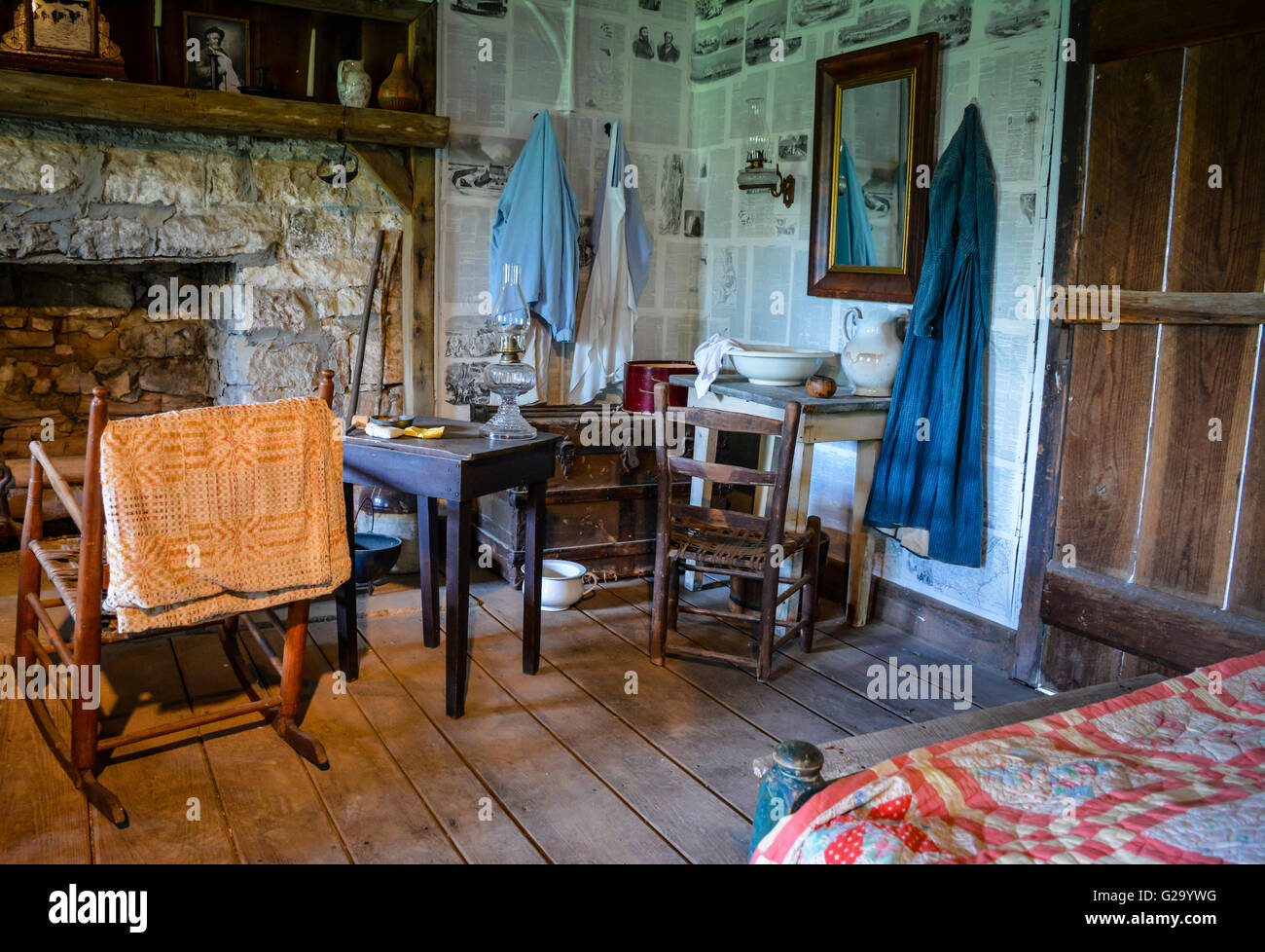 An Interior view of a rustically furnished log cabin with fireplace and furnishings depicting lifestyle of 19th - Stock Image