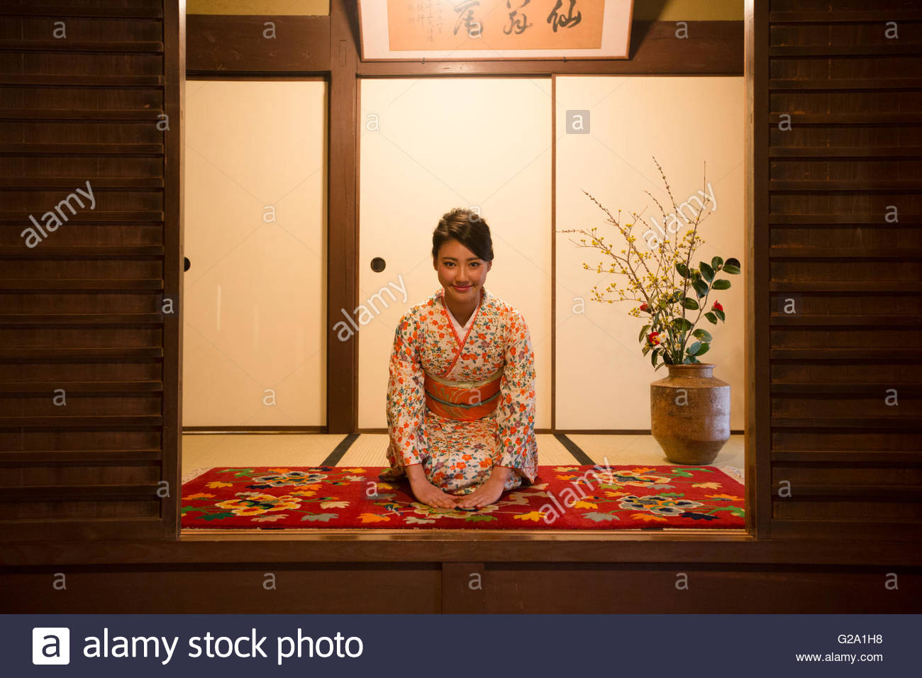 Young Japanese woman in kimono bowing - Stock Image