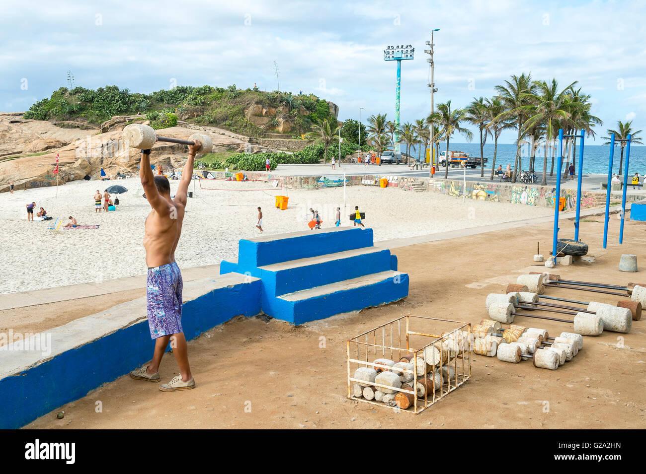 RIO DE JANEIRO - FEBRUARY 12, 2015: Brazilian man exercises at the outdoor workout station at Arpoador, the rock - Stock Image