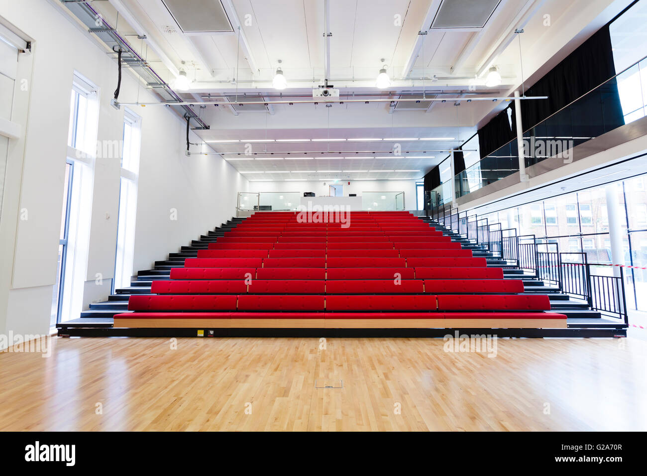 Open retractable seating at the school hall, Notting Hill and Ealing High School, Ealing, London, England - Stock Image