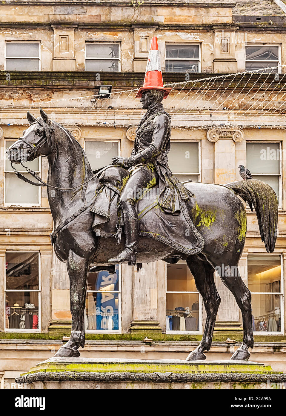 The Duke of Wellington statue in Glasgow, Scotland with its customary traffic cone on its head. - Stock Image