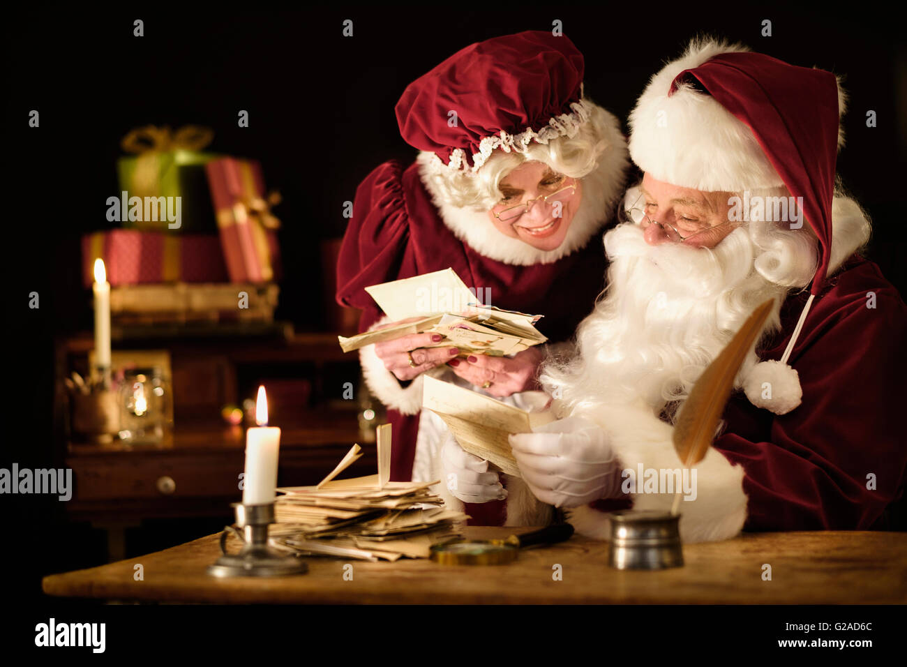 Santa and Mrs. Claus reading child's letter - Stock Image