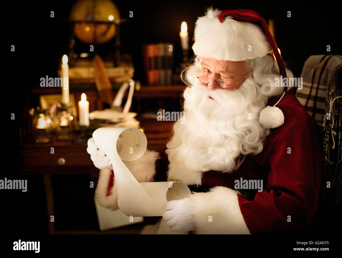 Portrait Of Santa Claus Reading ChildS Letter And Winking Stock