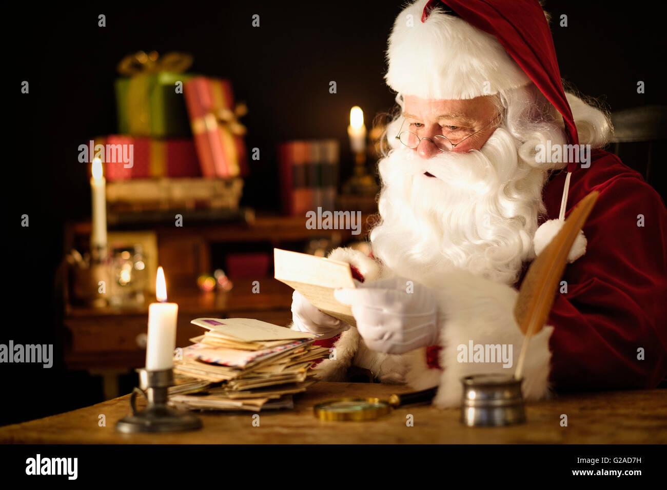 Portrait of Santa Claus reading child's letter at desk - Stock Image