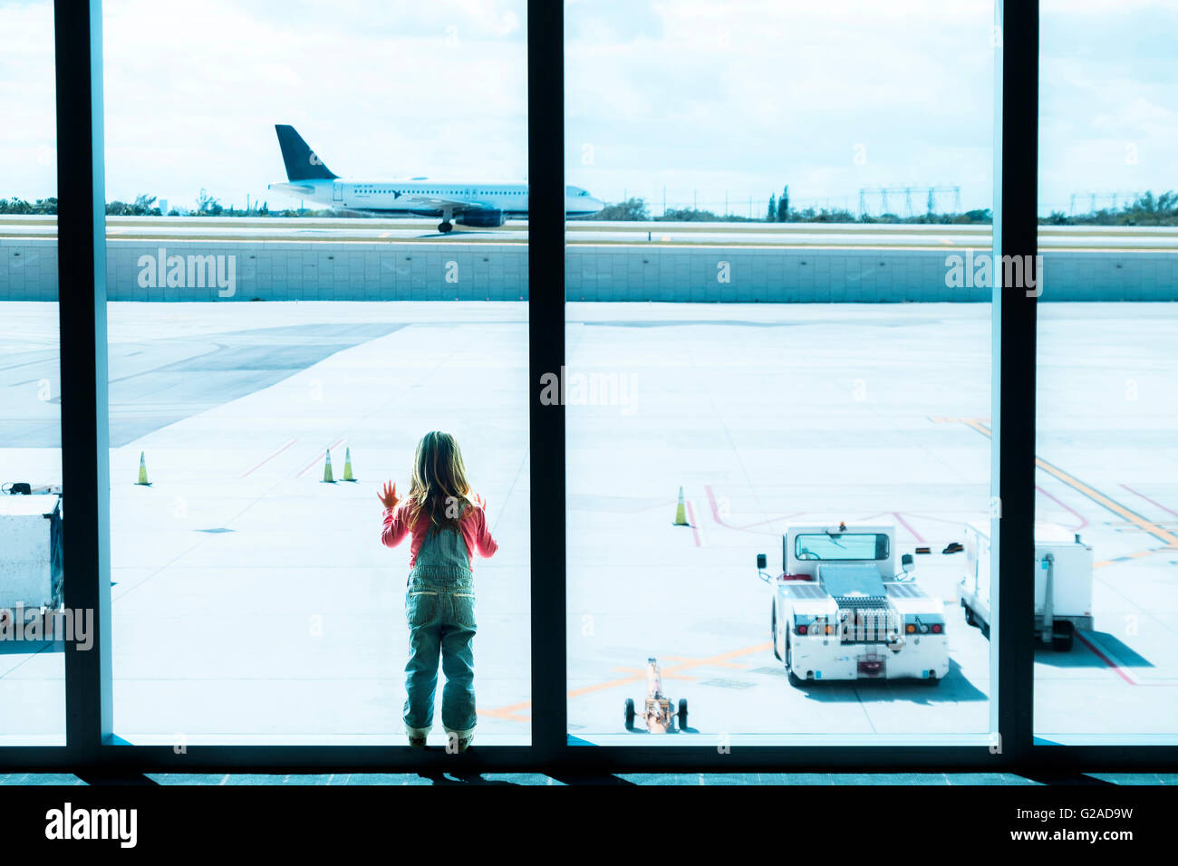 Girl (2-3) looking through window at airport - Stock Image