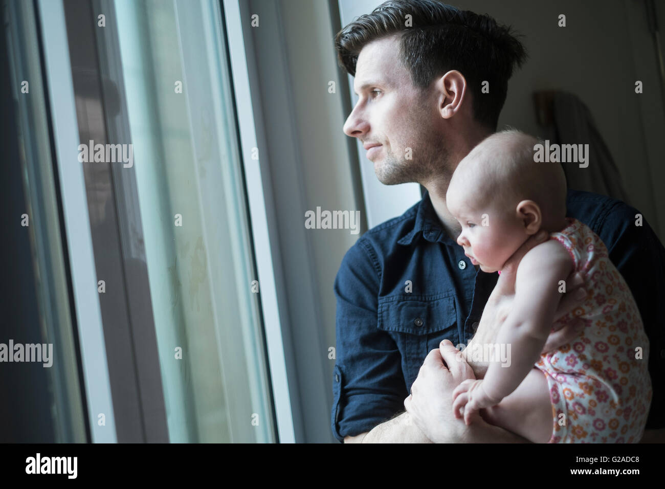 Father looking through window with daughter (2-5 months) - Stock Image