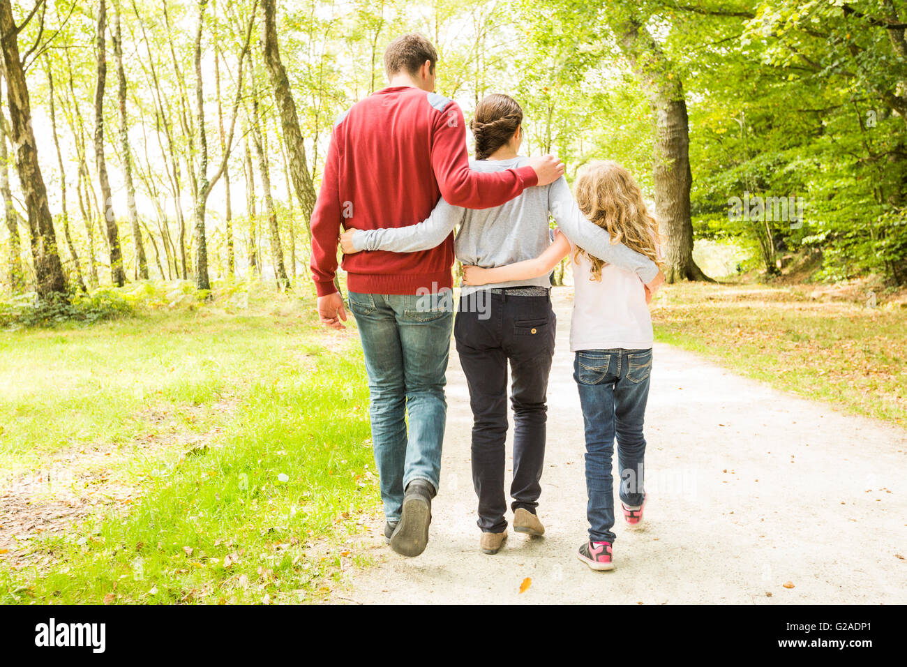 Daughter (8-9) with parents walking in park, rear view - Stock Image