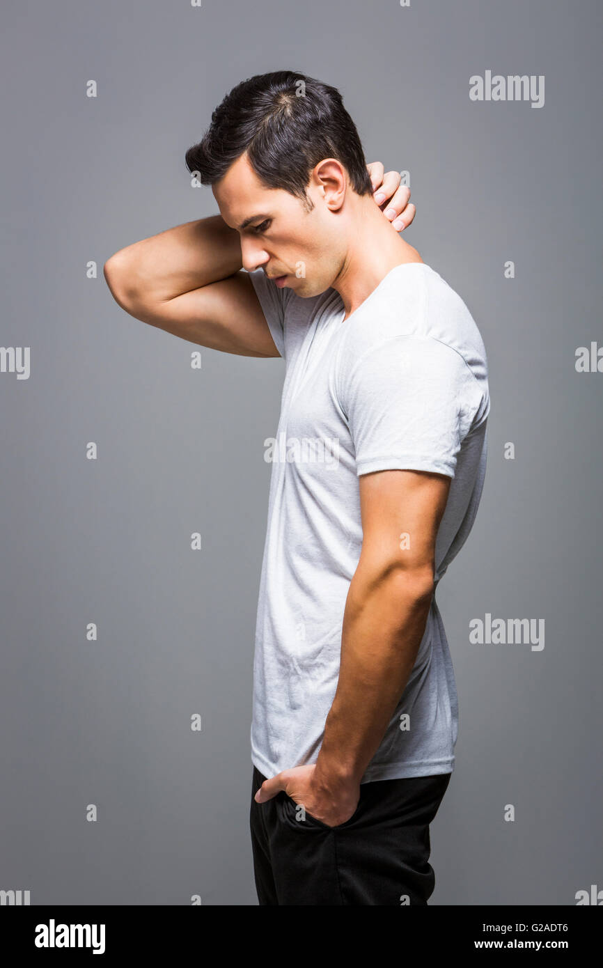 Man in white t-shirt on grey background - Stock Image