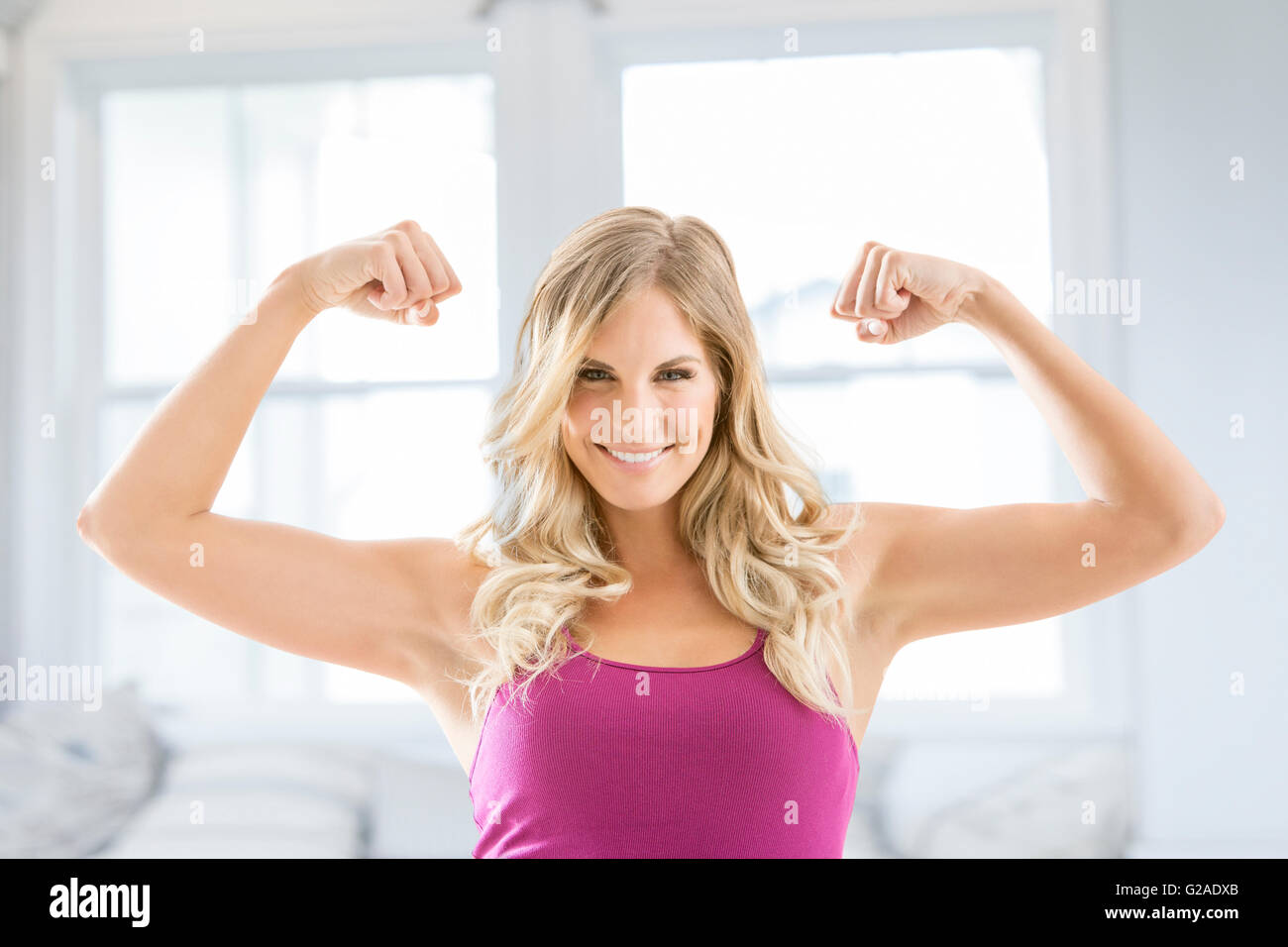 Smiling blonde woman flexing muscles - Stock Image