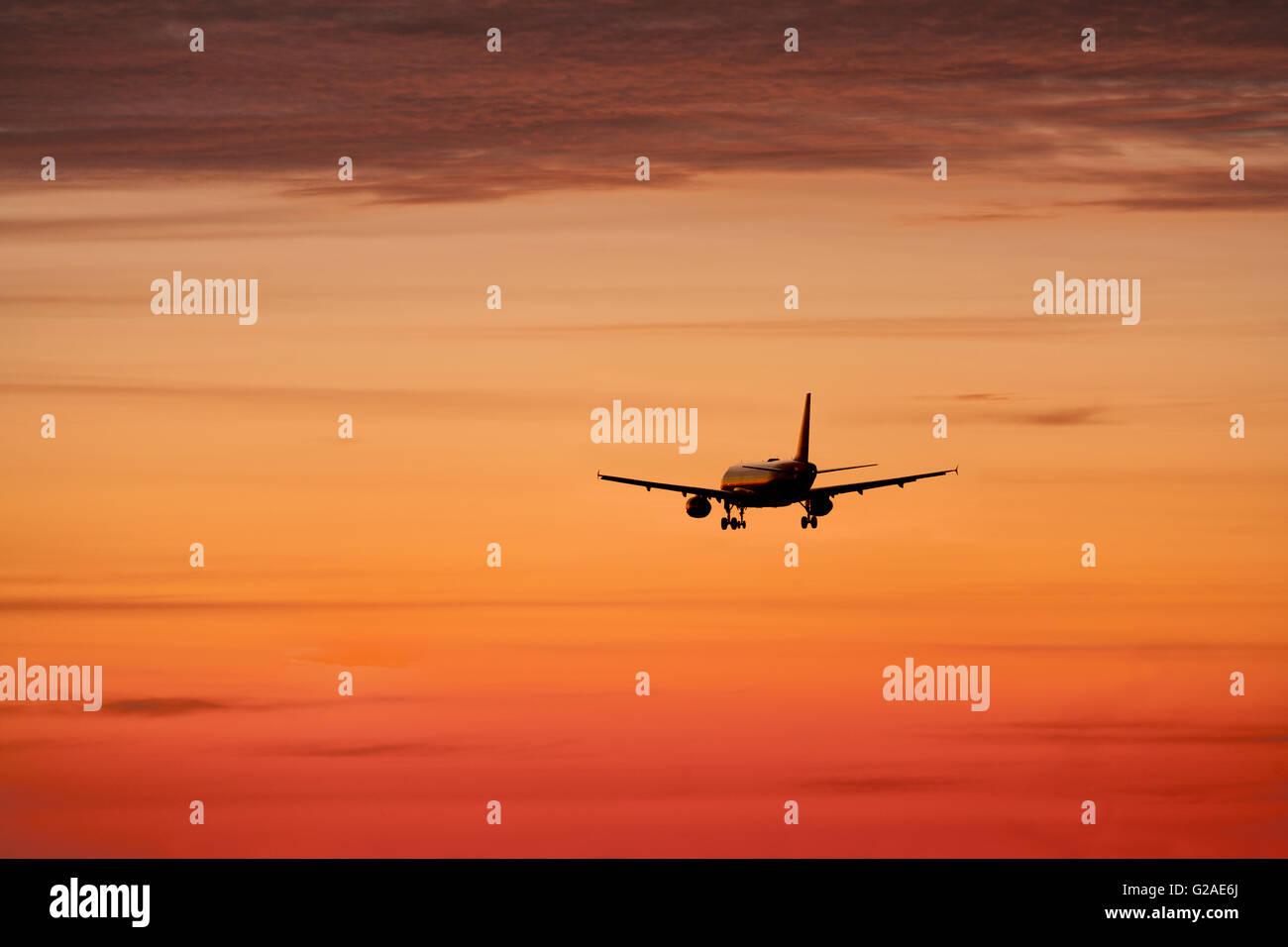 Airplane against orange sky - Stock Image